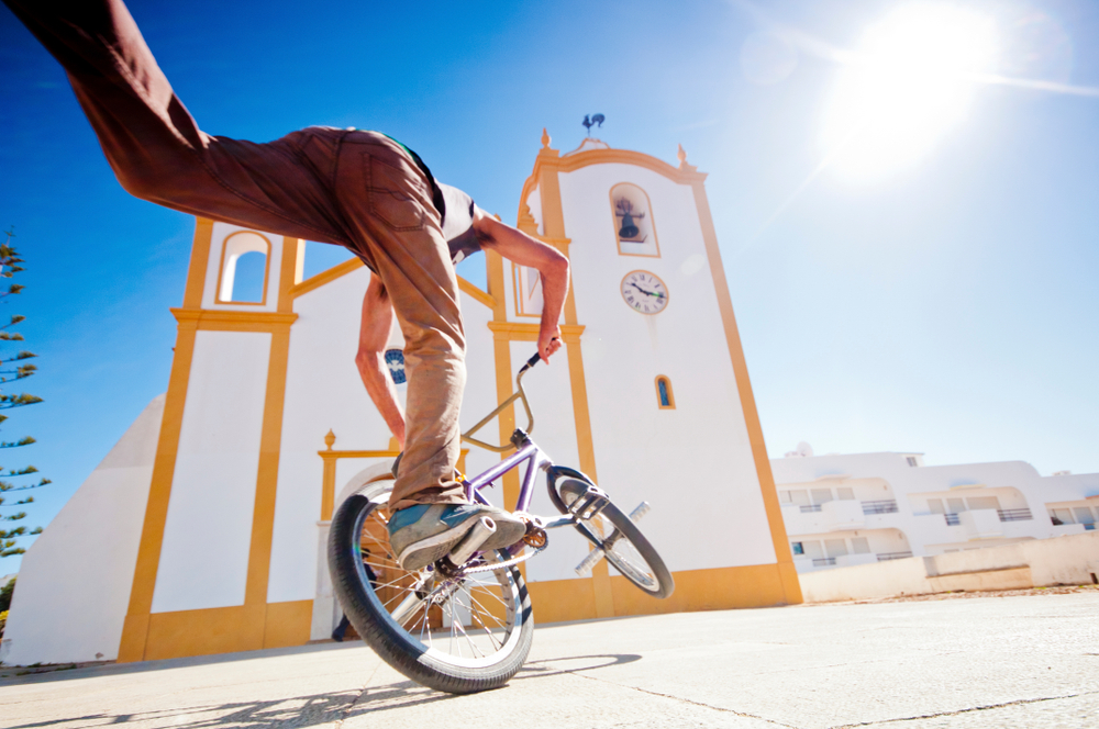 man riding on a bicycle doing tricks under the sun to display brightness and contrast meaning for photo adjustments